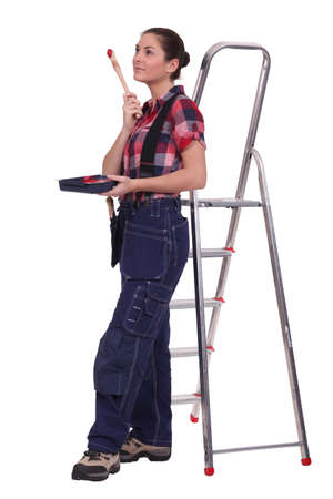 Young woman stood by ladder with paint brush Stock Photo - 13343858