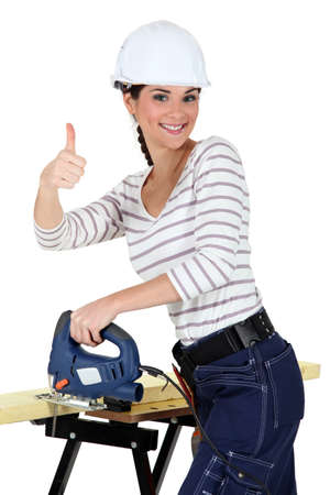Upbeat woman using band-saw photo