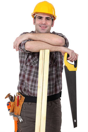 supported: Carpenter with wood slats and saw Stock Photo