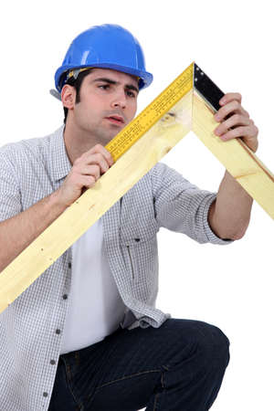 carpenter measuring a wooden frame photo