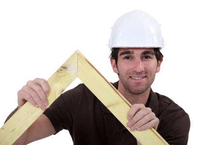 2x4 wood: Man building wooden truss