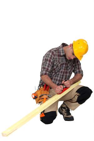 whittle: carpenter at work sharpening timber