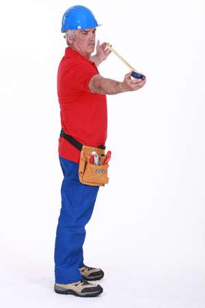 Senior plumber standing on white background photo