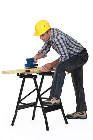 workmate: Carpenter using an electric sander Stock Photo
