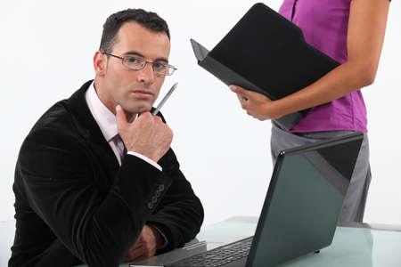 earnest: hombre de negocios buscando seriamente con la secretaria a su lado