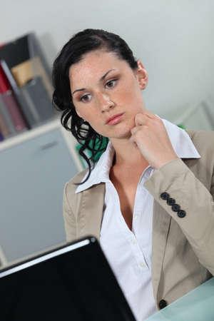 emotionless: Secretary staring at her laptop