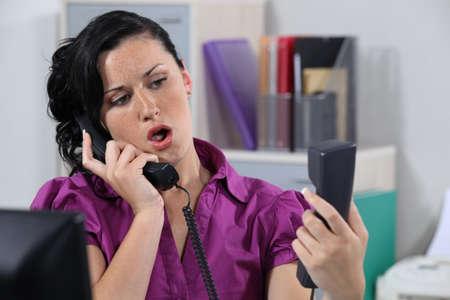 repondre au telephone: Agac� r�ceptionniste r�pondant t�l�phones qui sonnent Banque d'images