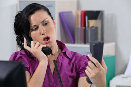 Annoyed receptionist answering ringing phones Stock Photo - 13344129