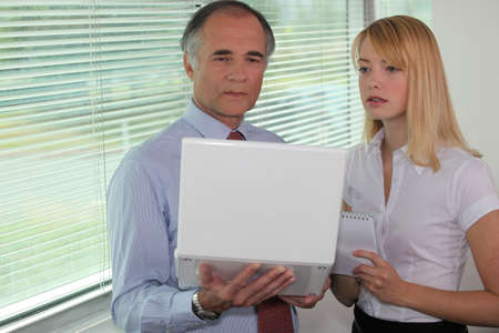 50 to 55 years old: Businessman looking at a laptop with his assistant Stock Photo