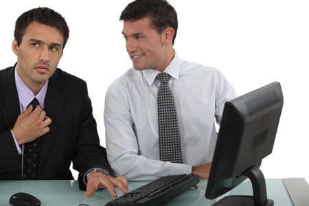 Man sat next to colleague adjusting tie photo