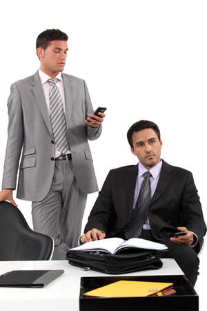 two businessmen sending messages on their cells Stock Photo - 13344208
