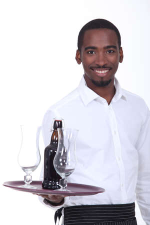 Black waiter carrying bottle of beer on tray photo