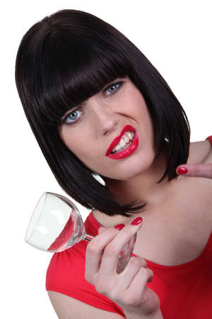 Woman in red with an empty wine glass photo