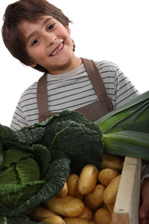 rascal: child standing behind vegetables Stock Photo