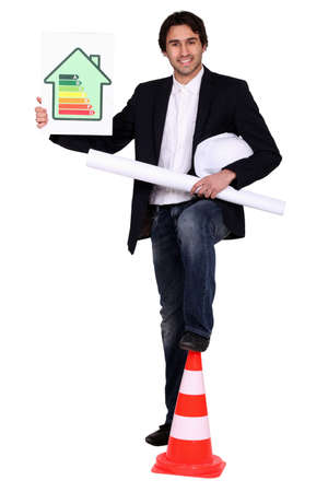 young architect posing with leg on construction cone photo