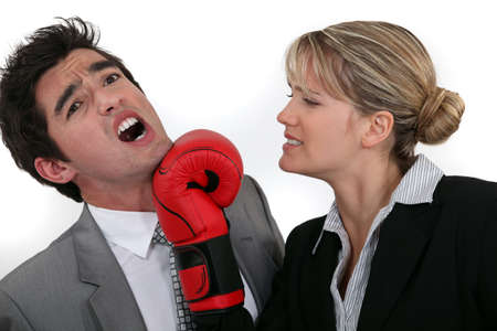 slap: businesswoman hitting a man with a boxing glove Stock Photo