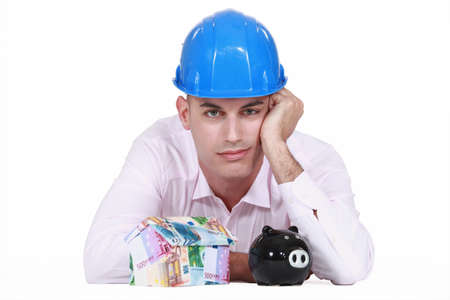 Jaded man posing with a piggy bank and a house made of money Stock Photo - 13343991