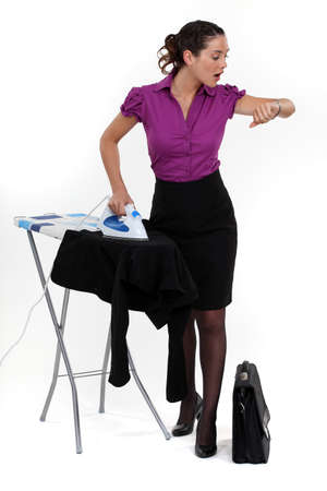 panicked: Businesswoman ironing and looking at the time