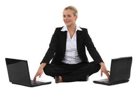 Woman sitting cross-legged in front of two computers photo
