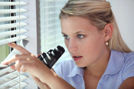 private investigator: A nosy woman spying Stock Photo