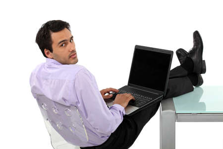 executive chair: Man resting feet on glass desk