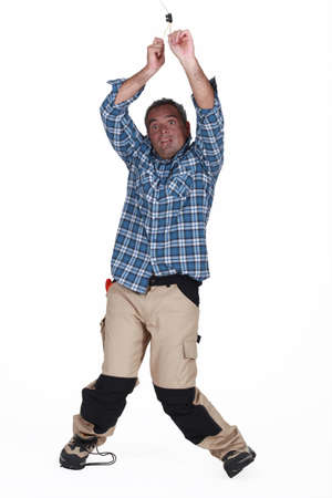 workmen: Electrician getting a shock from a light socket Stock Photo