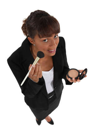 Businesswoman putting on makeup photo