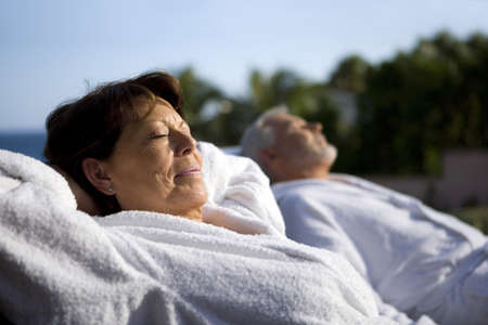 bath robes: Couple laying outside in bathing robes Stock Photo