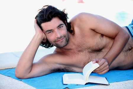 man with long hair: Man reading outside