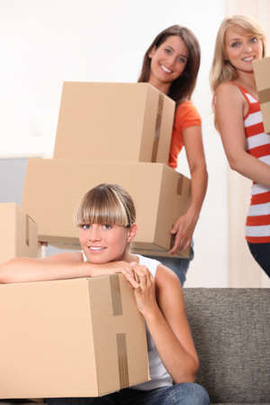Three female flat-mates packing boxes photo