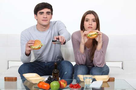 pareja comiendo: retrato de la joven pareja comiendo hamburguesas mientras ve la televisi�n