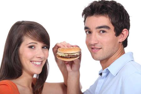 17: Studio shot of a young couple sharing a hamburger