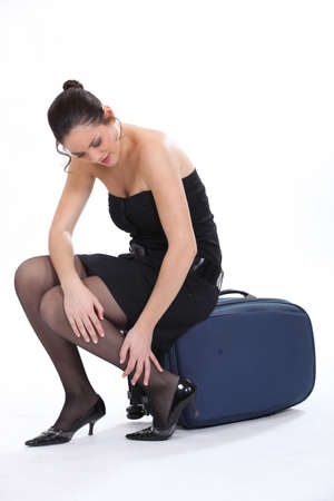 Woman sitting on a suitcase rubbing her ankle photo