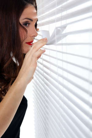 attach: Woman peering through some blinds