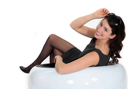 black stockings: Brunette woman sitting in white chair