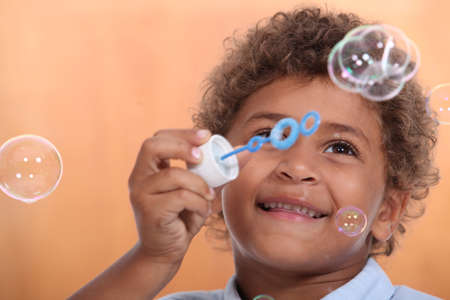 wee: Boy blowing bubbles Stock Photo
