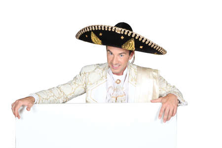 Man in a mariachi costume  with a board left blank for your  message photo