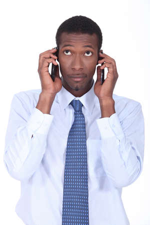 swamped: African businessman holding two telephones