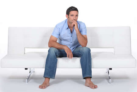 prudent: barefoot man sitting on a modern couch and wondering Stock Photo