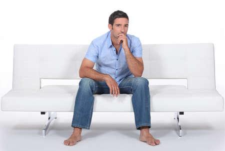 descalza: hombre descalzo sentado en un sof� moderno y pregunt�ndose