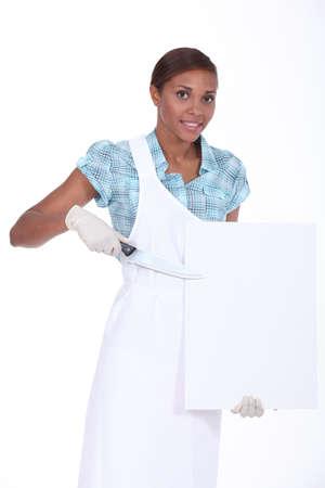butchering: female butcher holding a blank poster