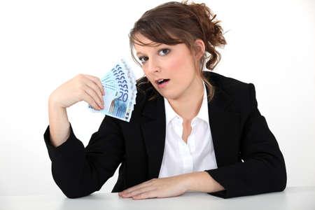 spendthrift: businesswoman holding bills Stock Photo