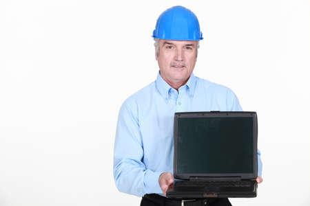 Architect stood holding portable computer photo