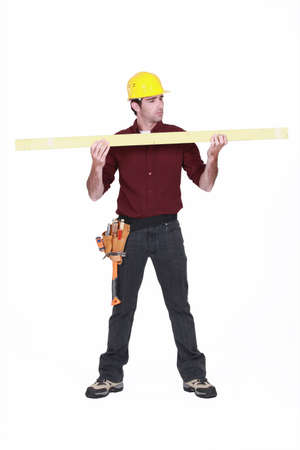 Carpenter holding a plank of wood photo