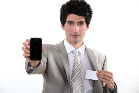 Businessman holding a blank business card and his phone Stock Photo - 13344199