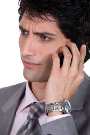 bummed: Frowning businessman using a cellphone