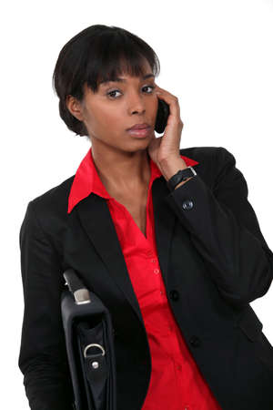 adaptable: Woman holding briefcase whilst on the telephone Stock Photo