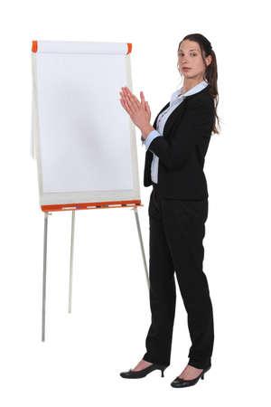 Brunette businesswoman debout par flip-chart
