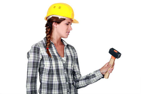 jaded: craftswoman holding a hammer looking fed up