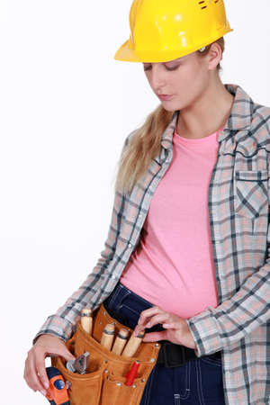 tradeswoman: Tradeswoman pulling a tool from her belt Stock Photo